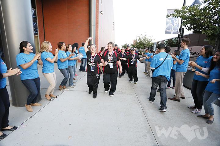WeLoveU volunteers cheering on participants