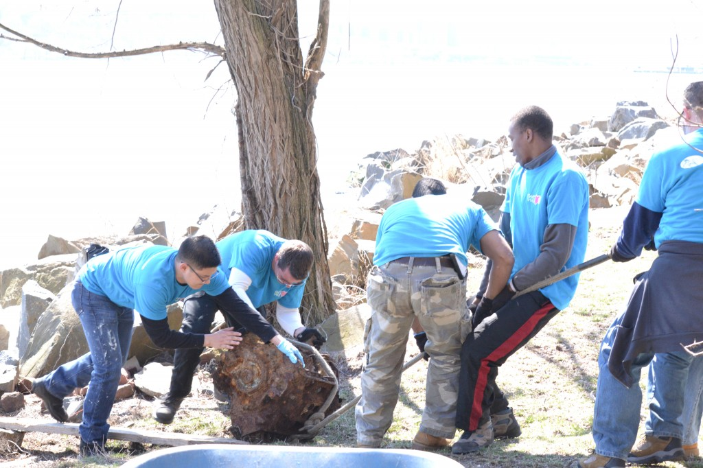 WeLoveU volunteers hauling out a rusted engine from the rocky shoreline.