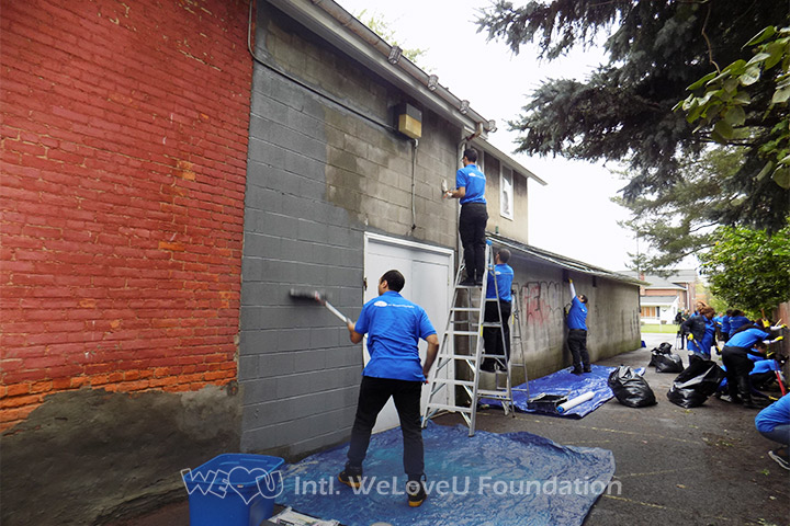 WeLoveU volunteers apply fresh paint to the sides.