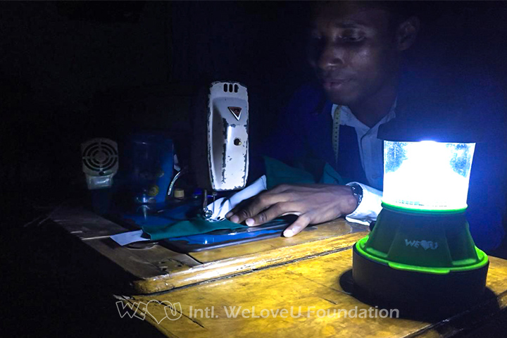 A student is sewing at night using the solar-powered lantern's light