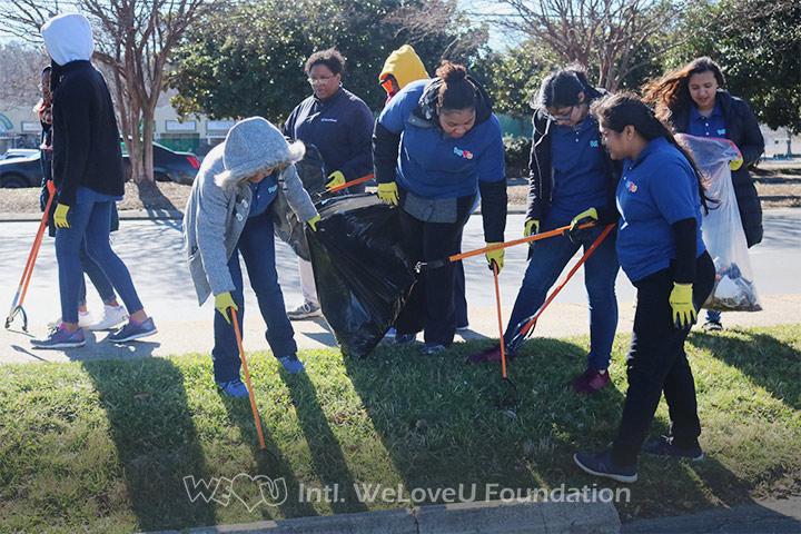 WeLoveU volunteers clean on the side of Albemarle Road