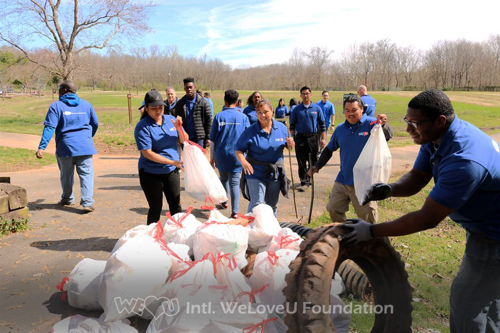 Volunteers gather all their filled trash bags into one pile
