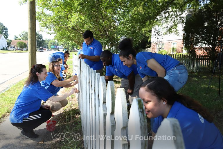 Volunteers painting Ms. Monroe's white-picket fence