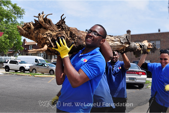WeLoveU volunteers move a heavy log