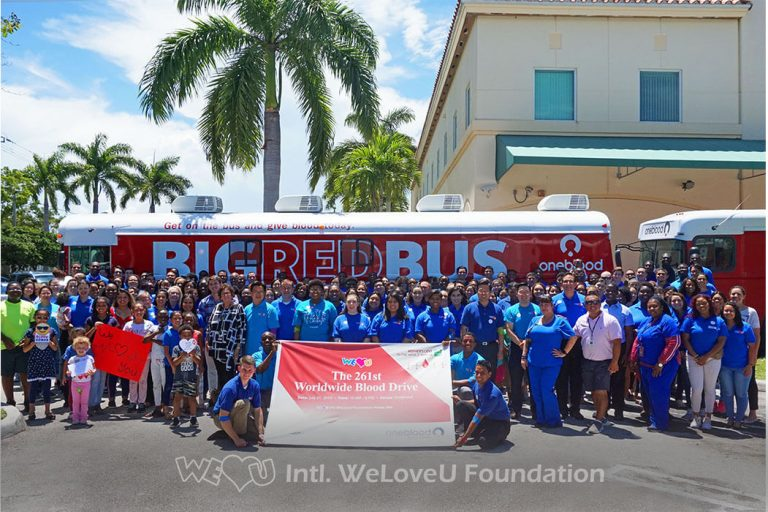 Volunteers who donated blood take group photo outside of OneBlood's donation bus