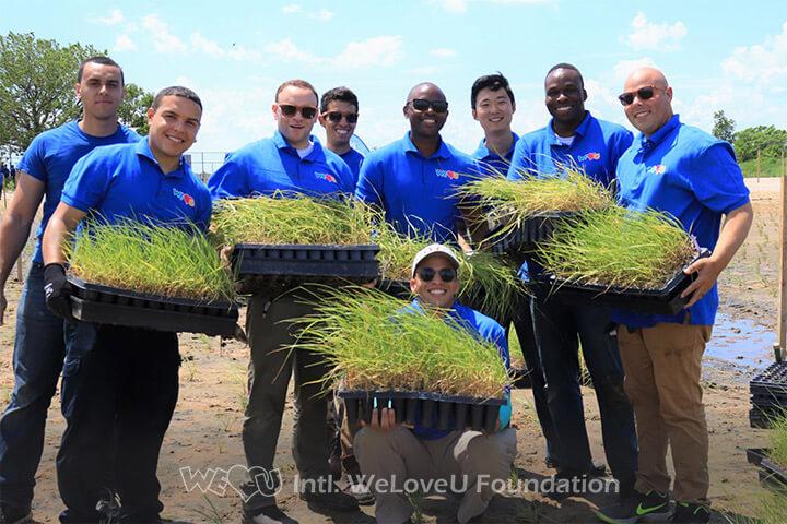 WeLoveU Foundation volunteers carrying cartridges of marsh plugs