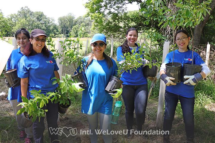 WeLoveU Foundation volunteers holding plants