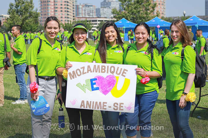 A group of WeLoveU volunteers with a sign in support of Mozambique.