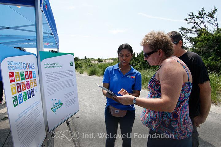 Beach goers reading WeLoveU Foundation panels
