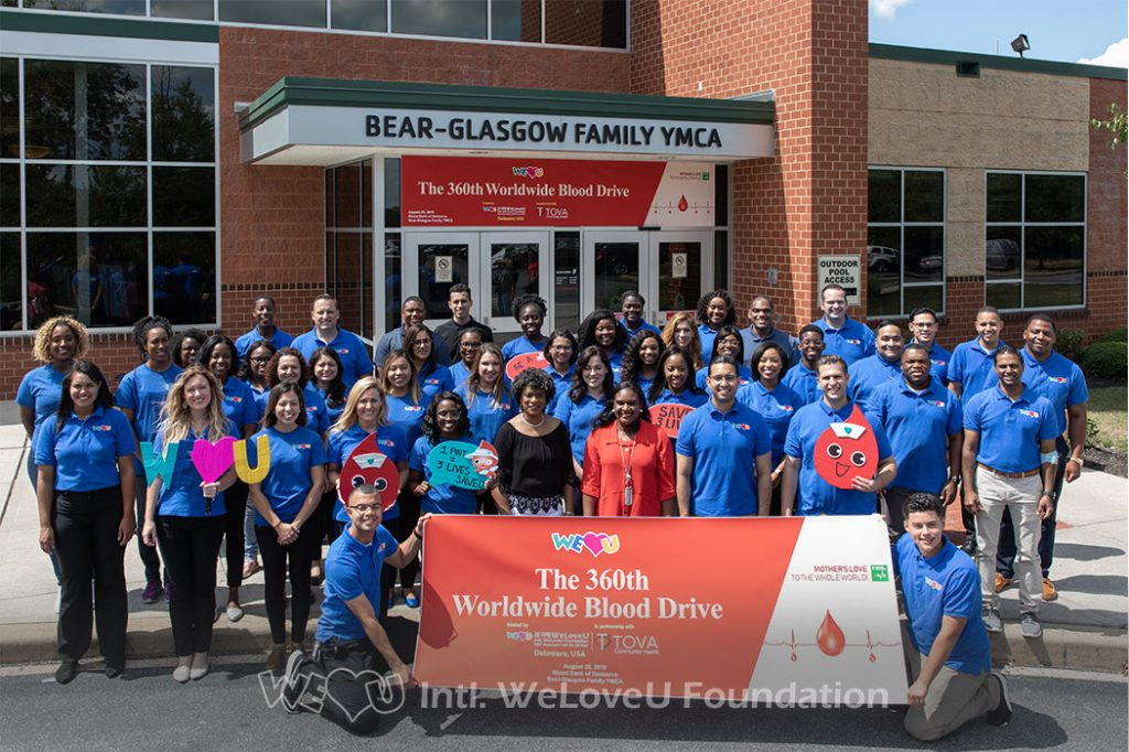 group photo of weloveu volunteers, Dr. Nina Anderson, and City Treasurer Velda Jones-Potter outside the Bear-Glasgow YMCA in Newark, DE