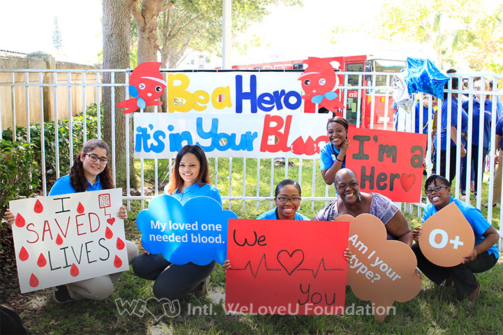 WeLoveU volunteers sitting outside with signs