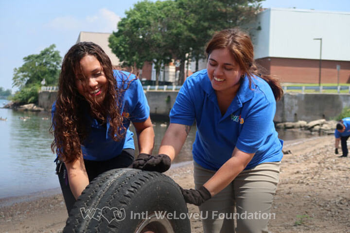 rolling a tire, working together, unity, volunteers