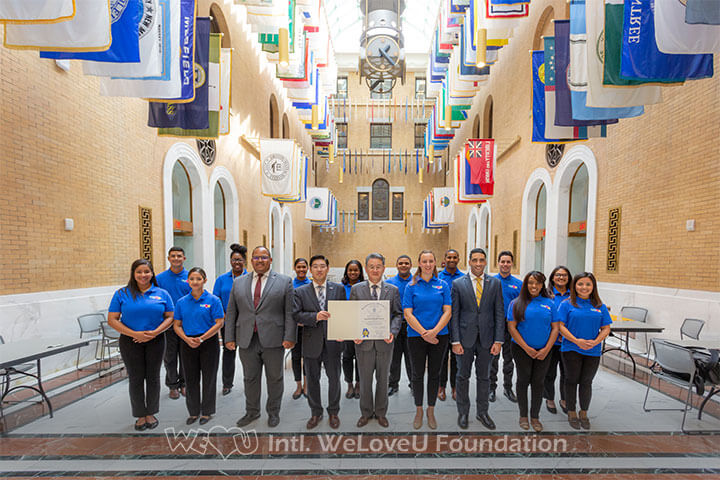 The President of the Intl. WeLoveU Foundation East Coast Region and volunteers take a group photo with the Citation.