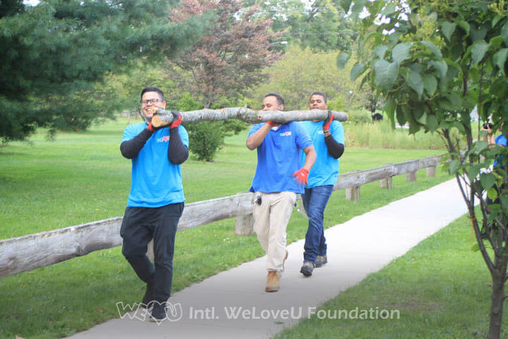 A trio of WeLoveU volunteers picking up dead branches