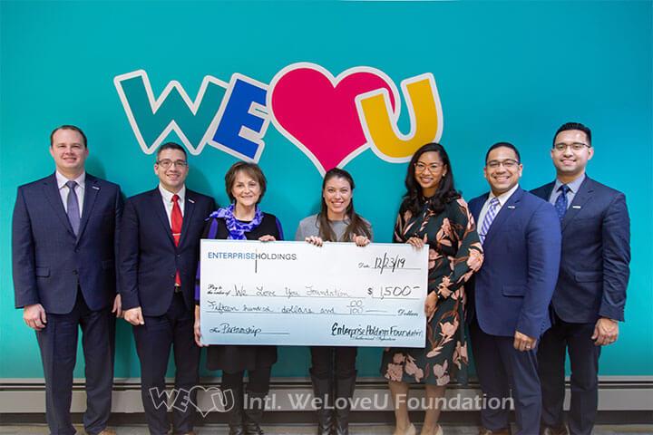 Enterprise Holdings representative presents check donation to the WeLoveU Foundation